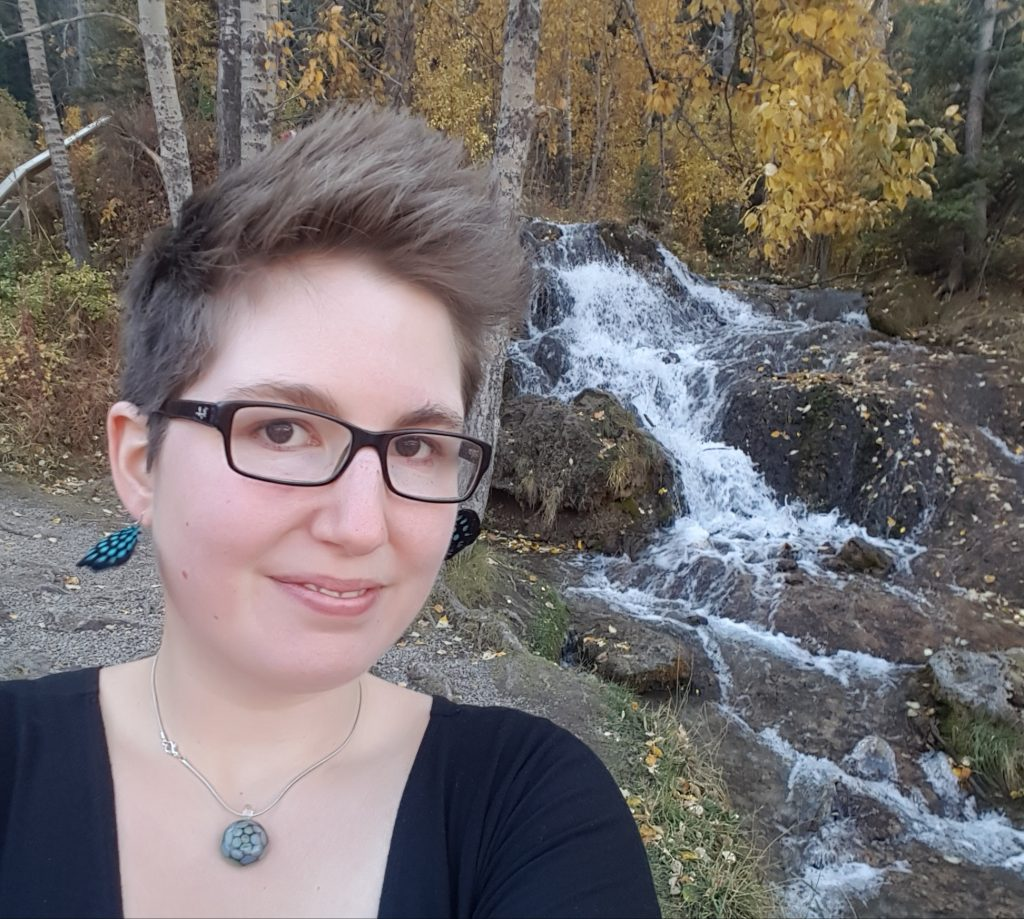 Amie Hicks. Casual portrait photo in front of waterfall.